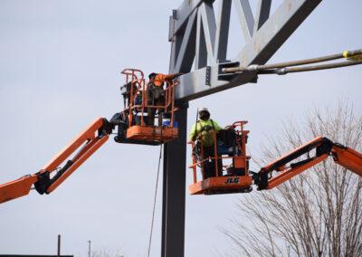 New UWL Fieldhouse 2021 • New UWL Fieldhouse 2021 • Workers on cherry pickers installing truss